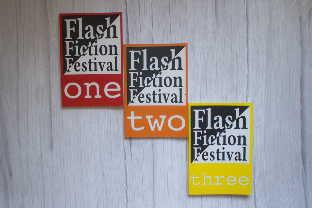 Three books, red, orange and yello with Flash Fiction Festival written on the cover